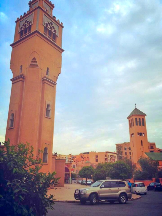 A picture with two tall narrow dark orange buildings. They are across the street from each other and cars are parked by the curb. One building is a church as indicated by the cross at the top and the other building is a mosque. The picture was taken in Marrakech, Morocco.