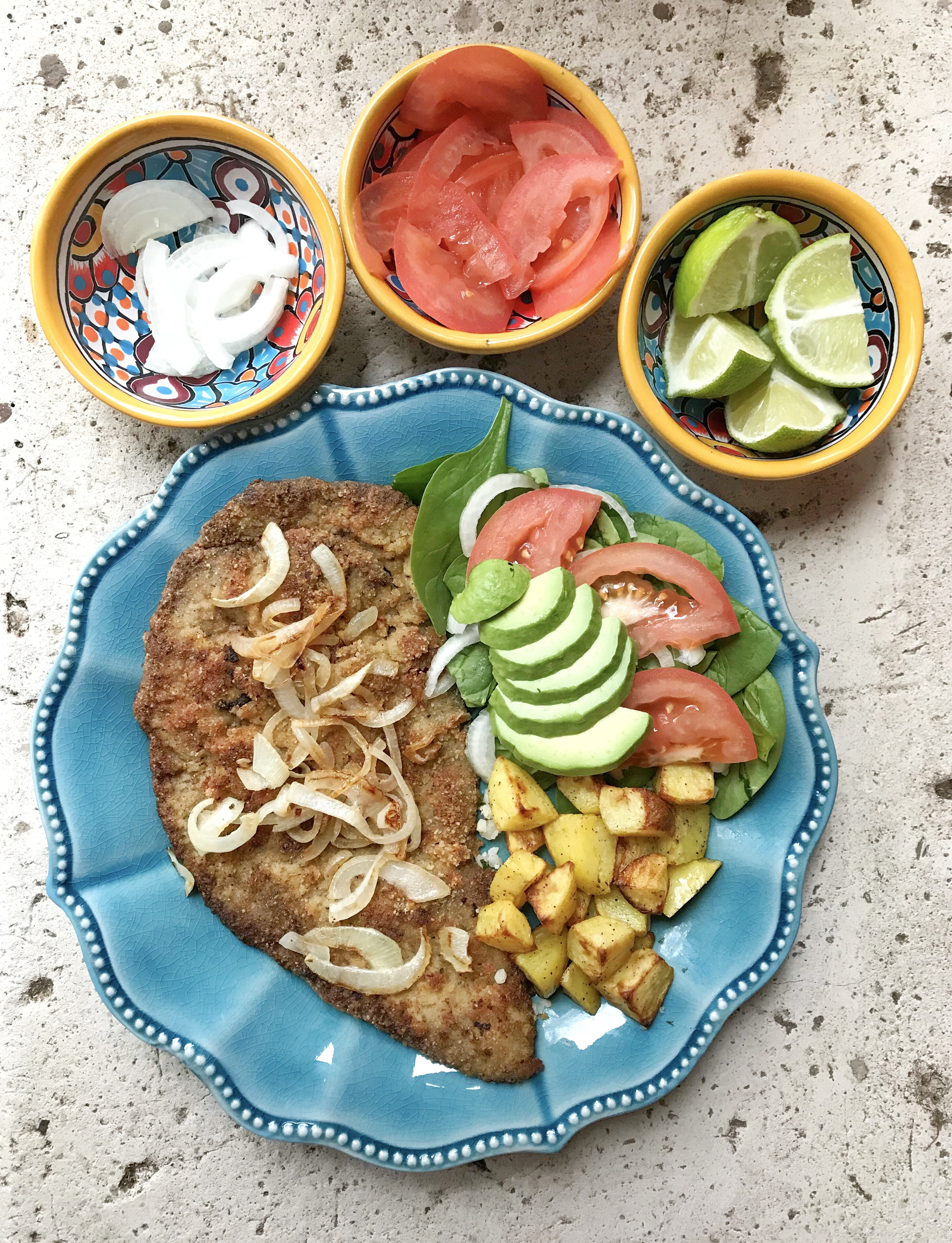 A plate with a milanesa steak topped with sauteed onions. There is a salad as a side with tomatoes, spinach, onions, and avocado. The other side served on the plate is roasted golden potatoes. There are three small condiment bowls with Mexican decorations holding onions, tomatoes, and lime wedges.